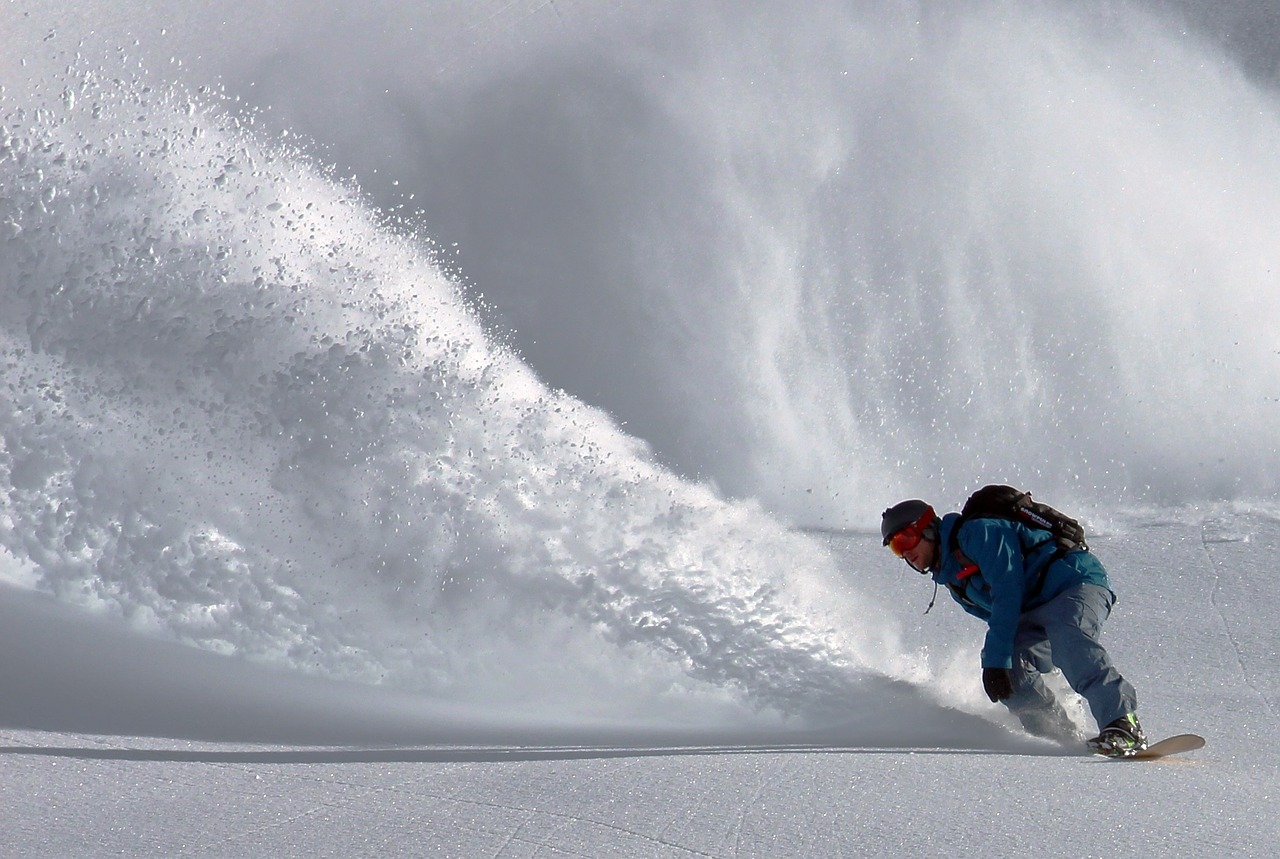 Snowboarding - A snowboarder carves his way down the mountain