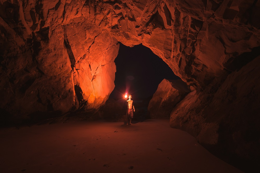 A man with a torch explores a cave.