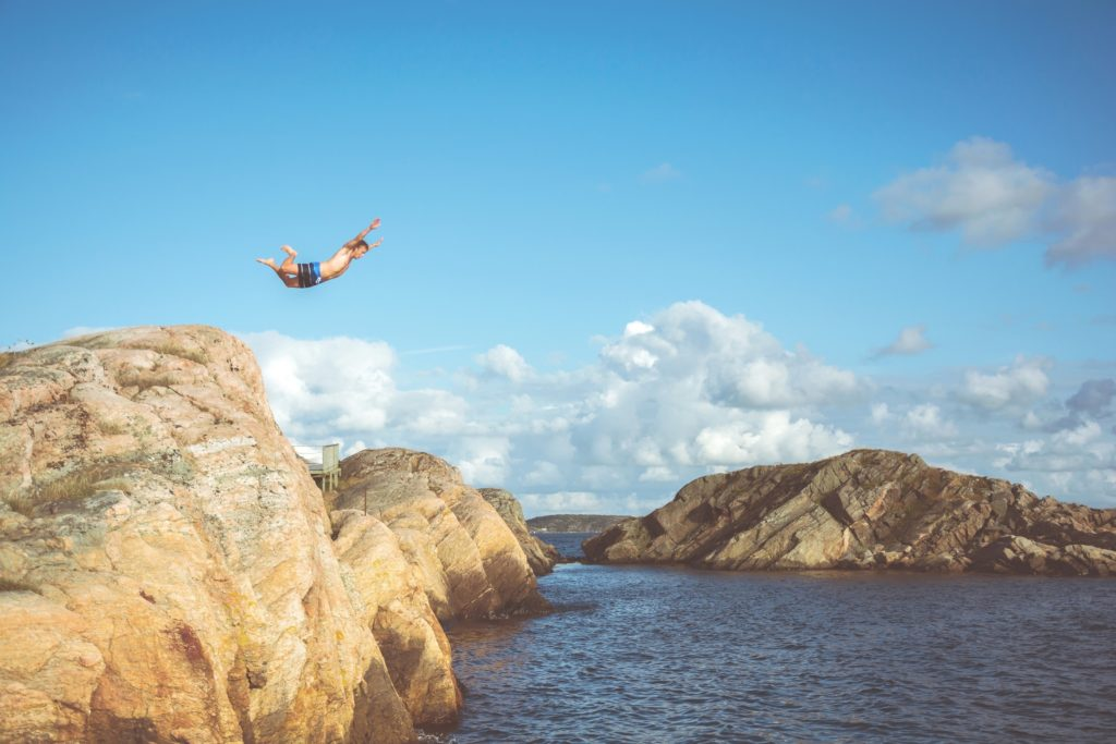 Cliff Diving in Delaware - A man jumps from a cliff into a lake.